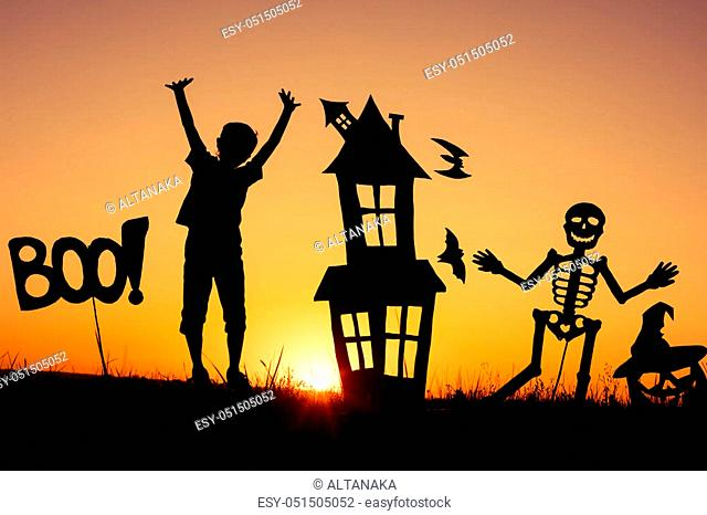 Happy little boy playing outdoors at the sunset time. Kid having fun. Concept of happy Halloween party