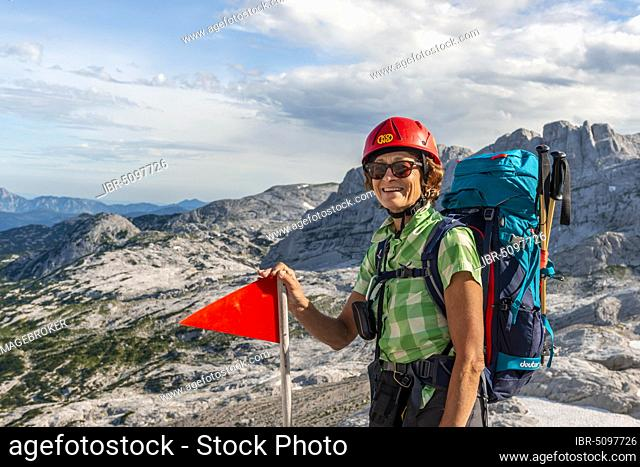 Mountaineer with backpack and helmet looks happily into the camera, route from Simonyhütte to Adamekhütte, rocky alpine terrain, Salzkammergut, Upper Austria