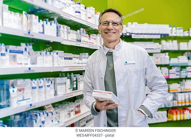 Portrait of smiling pharmacist holding medicine in pharmacy