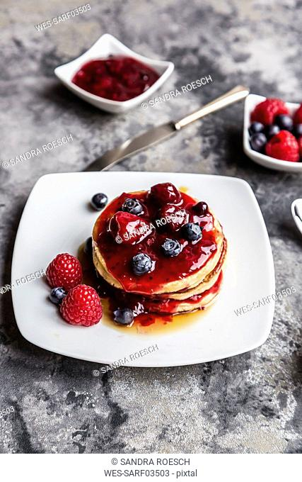 Pancakes with red fruit jelly, maple sirup, raspberry and blueberry