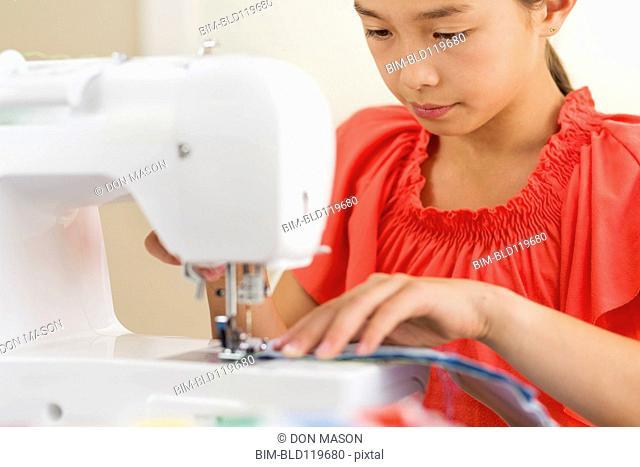 Mixed race girl using sewing machine