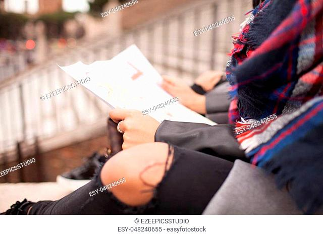 Caucasian hipster woman taking a break and reading map outside in the city