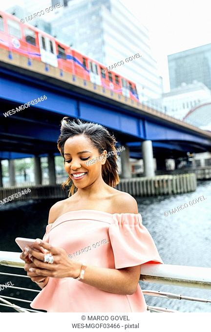 Smiling woman sending messages with her smartphone in the city