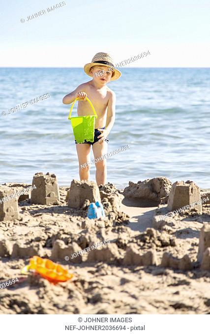 Boy on beach making sandcastles