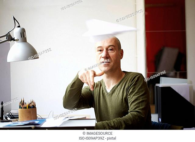 Mature man at desk throwing paper airplane
