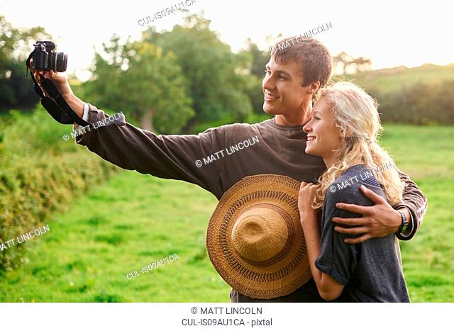 Young couple taking self portrait in rural field