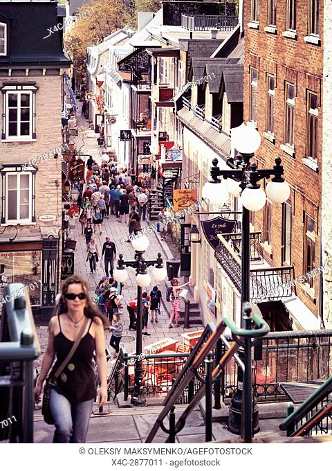 Young woman walking up the stairs of historic street Rue du Petit Champlain on a sunny day. The high angle view of the vibrant shops and restaurants in the...