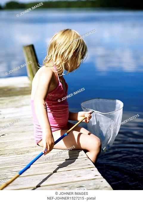 Girl sitting on jetty with fishing net