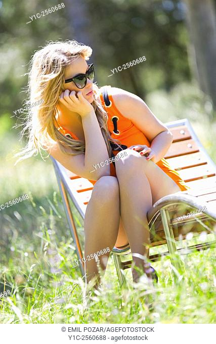 Young woman on wooden park deckchair