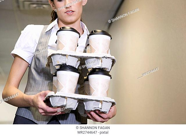 Woman carrying coffee cups