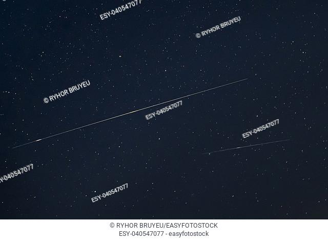 Two Meteoric Tracks In The Blue Night Starry Sky Background. Natural Glowing Stars And Meteorites Trails