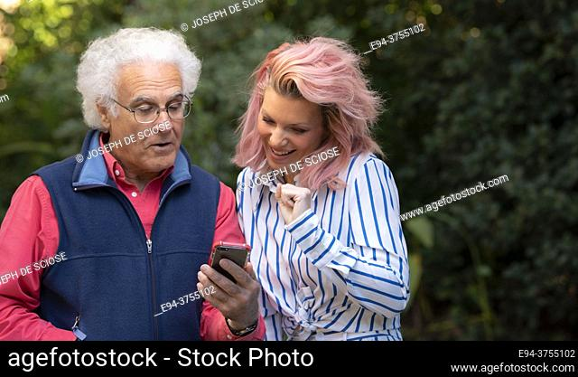 A pretty 34 year old blond woman talking and looking at a cell phone with a 67 year old man