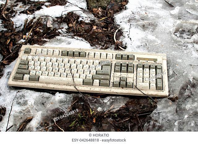 Abandoned dirty broken grunge computer keyboard on snowy frozen soil