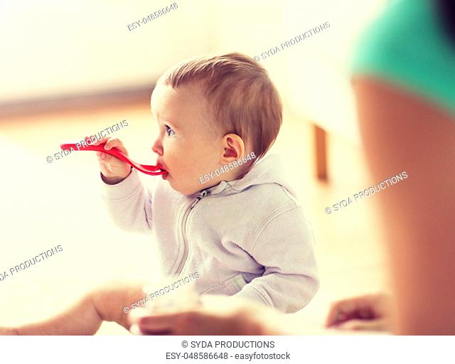 mother and baby with spoon eating at home