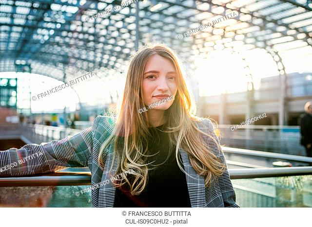 Young woman with long blond hair in sunlit train station, portrait, Turin, Piemonte, Italy