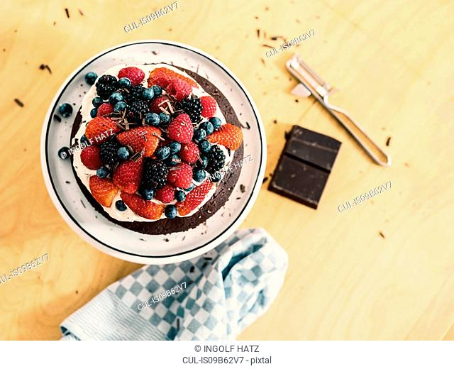 Chocolate cake decorated with cream, fresh summer fruits and chocolate
