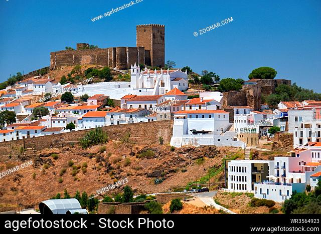 The mediaeval castle on the top of the hill surrounded by residential Alentejo country-style houses inside the old city walls of Mertola