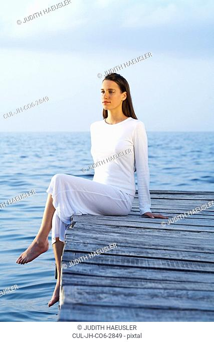 Young woman sitting on dock looking at sea