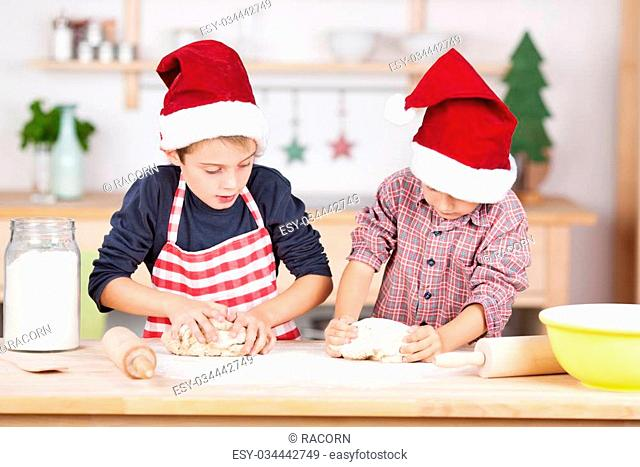 Two young brothers in colourful festive red Santa hats baking Christmas cookies standing side by side at the kitchen counter each kneading their pastry