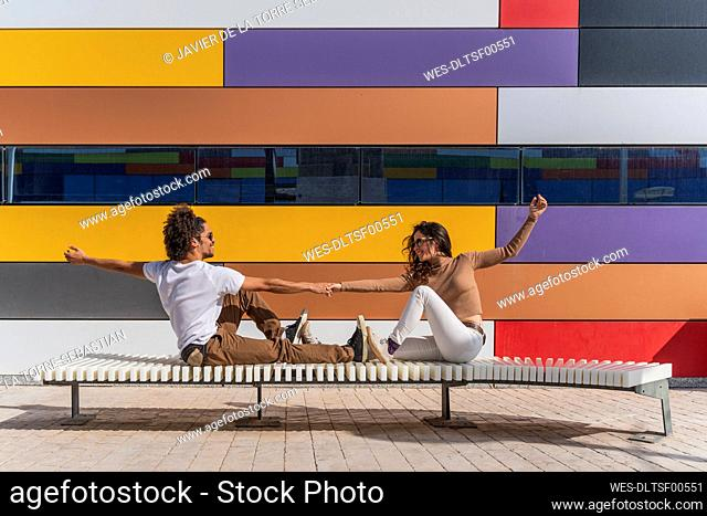 Dancers practicing on bench in front of colorful wall