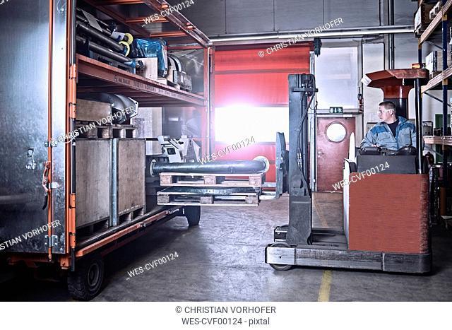 Fork-lift driver loading trailer