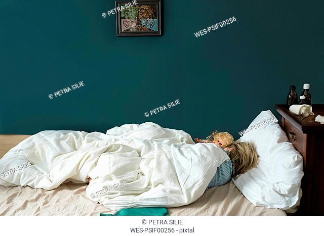 Sick girl lying in bed with doll