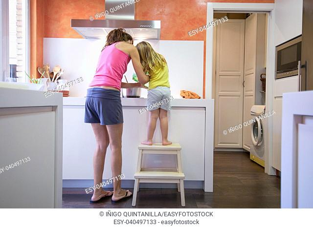 Funny scene. Woman mother and four years old blonde child on stool o ladder cooking together as a team, in electrical cooktop with a saucepan, in the kitchen