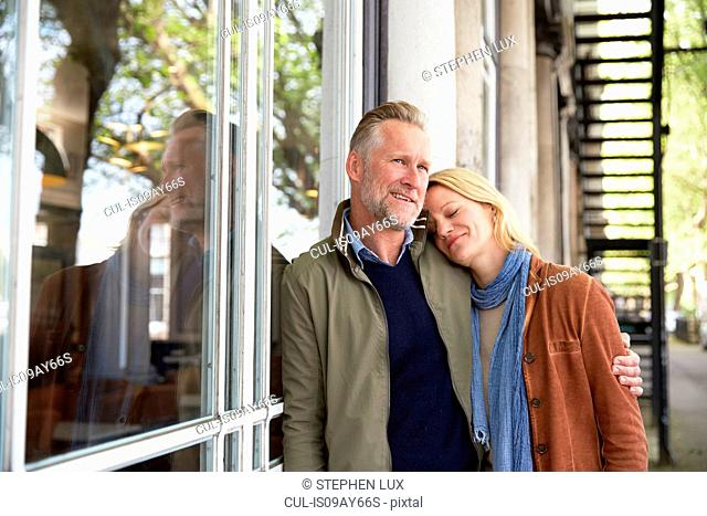 Mature couple leaning against window smiling