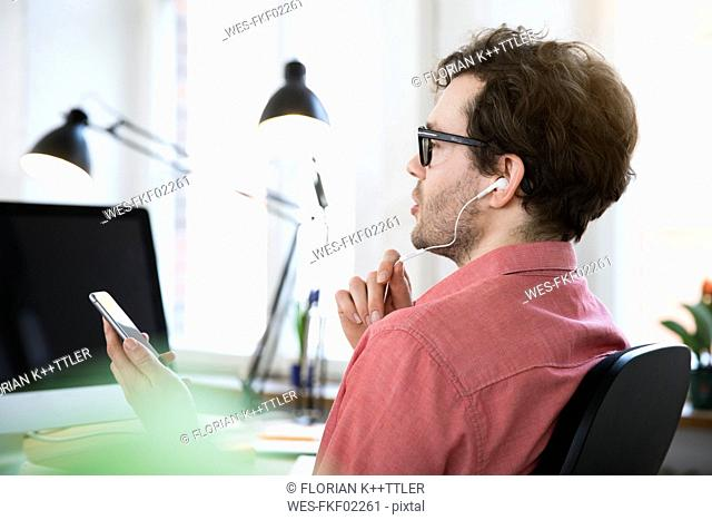 Man with earphones using cell phone in office