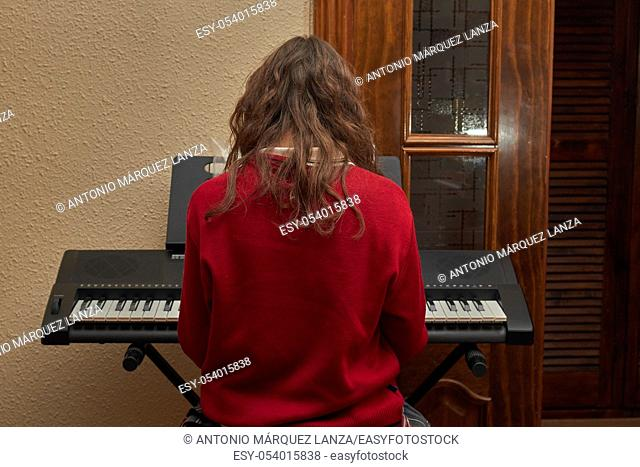 girl playing piano in her house