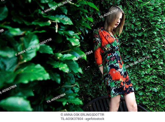 Lone female figure wearing summer dress by hedge