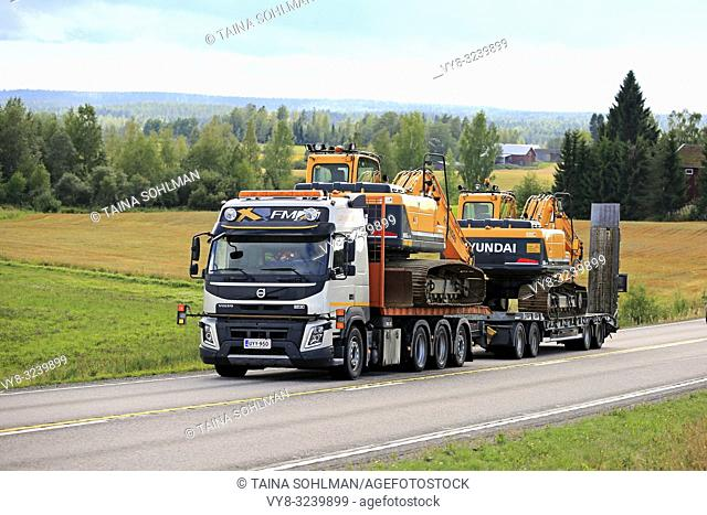 Jamsa, Finland - August 23, 2018: Volvo FMX truck hauls two Huyndai Robex 180 LC-9 and 160 LC-9 crawler excavators on trailer along road as wide load