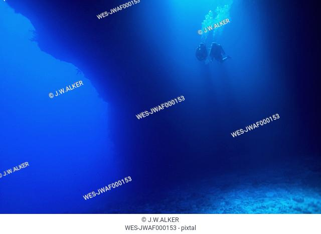 Palau, Pacific Ocean, two scuba divers in underwater cave