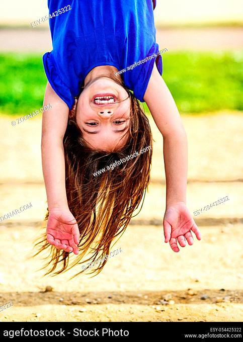 beautiful portrait of cute child hanging upside down on the monkey bars