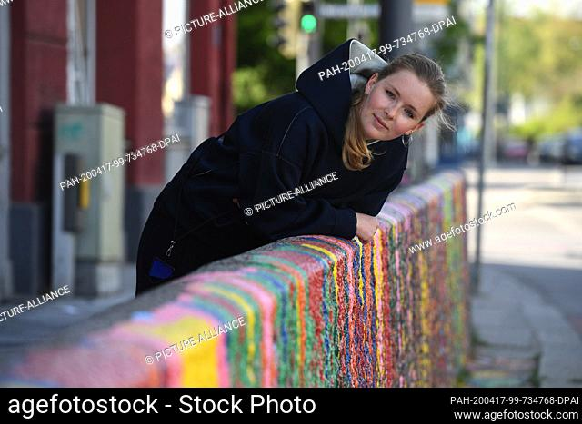 "17 April 2020, Bavaria, Munich: The artist Janine Mackenroth bends over her still unfinished work entitled """"Ein Viertel läuft über"""""