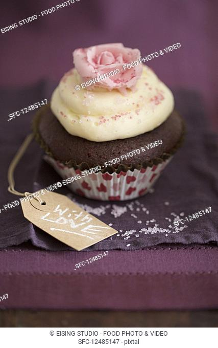 A chocolate cupcake with vanilla cream and a sugar rose