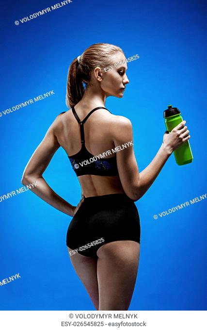 Muscular young woman athlete drinking water on blue background