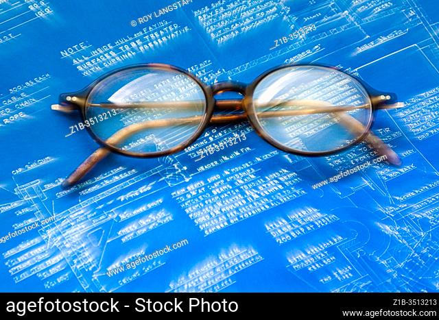 Old style eye glasses on a blurred Blue Print indicating a new prescription is required
