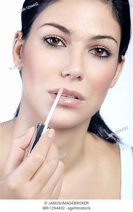 Young woman applying lip gloss, looking directly at the viewer, beauty