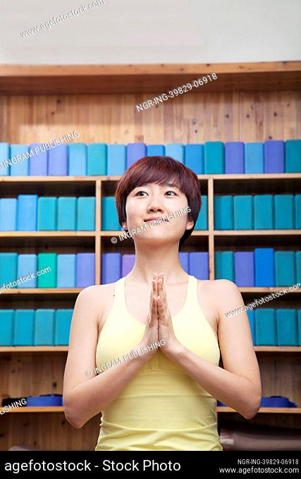 Portrait of young woman with short hair doing yoga with hands clasped together in front