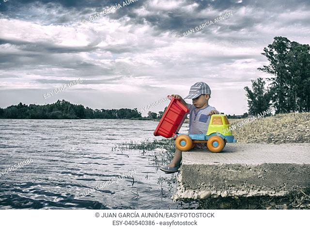 Two year old boy playing at riverside with dump truck. He is unloading stones on water