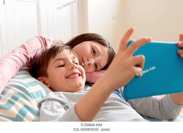 Boy and sister reclining on beanbag chair looking at digital tablet