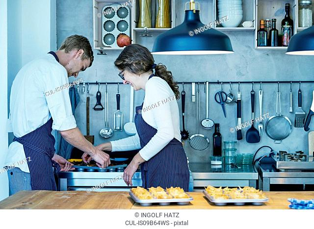 Two chefs in kitchen, removing freshly baked canapes from baking tray