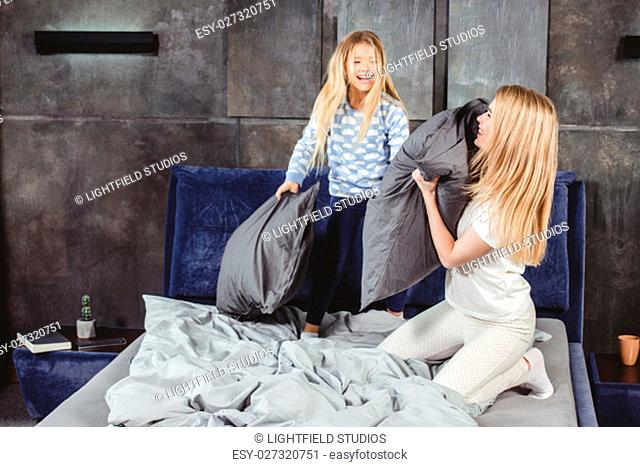 Happy mother and daughter fighting with pillows on bed in bedroom