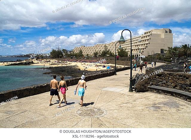 COSTA TEGUISE LANZAROTE Beach front Tourists walking along promenade Teguise Playa hotel