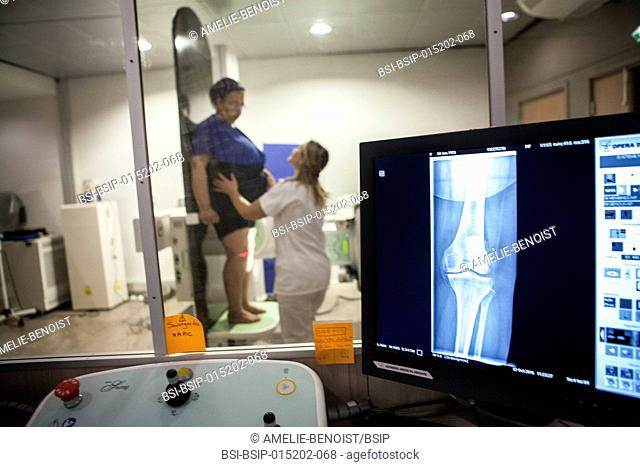 Reportage in a radiology centre in Haute-Savoie, France. A technician carries out a knee x-ray on a patient with the beginnings of osteoarthritis