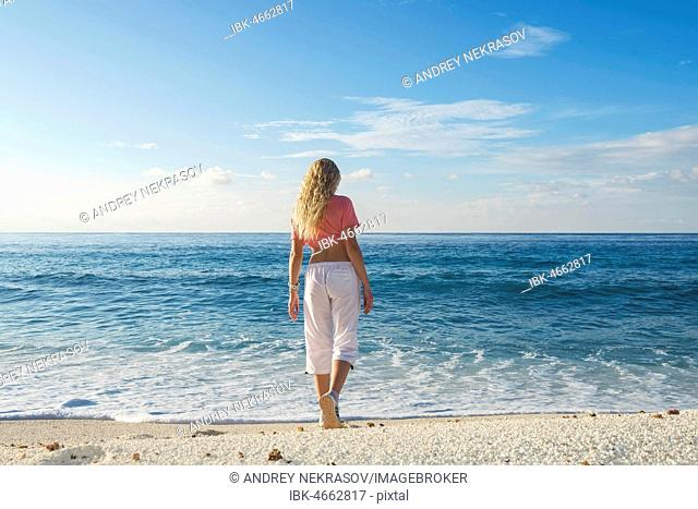Young woman goes to the surf on a sandy beach, Fuvahmulah Island, Indian Ocean, Maldives