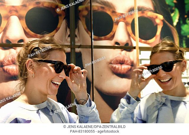 Cora Wollenstein, employee at 'Ace and Tate', tries on glasses in the flagship store of the Dutch glasses brand 'Ace and Tate' in Neue Schonhauser Strasse in...