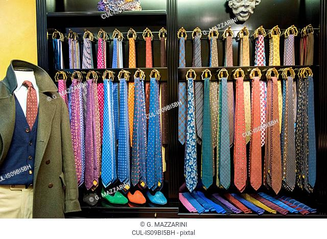 Rows of ties and tailors dummy in traditional tailors shop