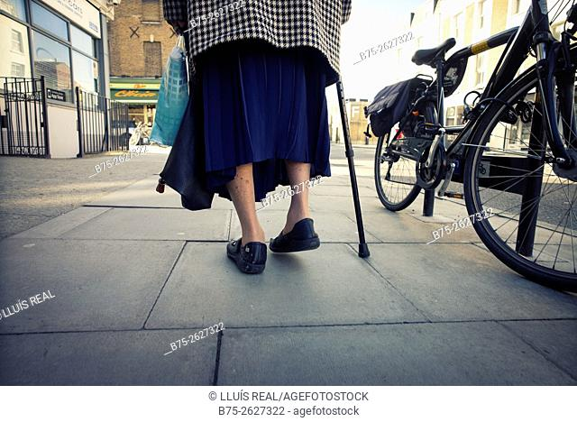 Close up of the legs of an old lady walking in the street with stick next to a parked bike